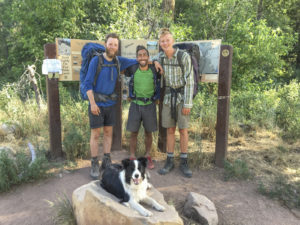group in front of trail sign with dog resting on rock