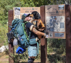 dog licking owner at trail sign