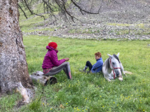 two women sitting with horse lying down
