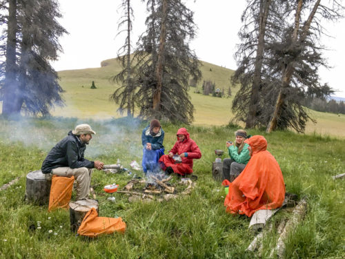 group sitting around small fire