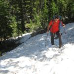 Thru-hiker struggling in deep snowpack on north-facing and tree-shaded slopes.