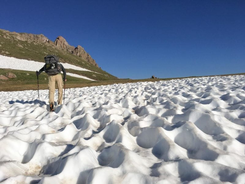 hiker in sun-cupped snow