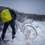 Alt - Bicyclist wearing big yellow pack fiddles with a snow covered bike.