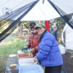 Trail crew members washing dishes just outside of tent