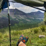 Looking out from tent at colorful socks and mountains