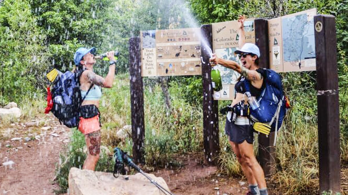 Two women backpackers celebrate completing The Colorado Trail at Junction Creek Trailhead near Durango. Champagne!