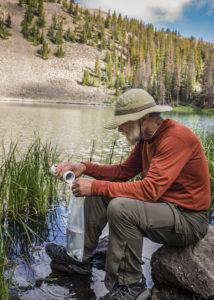 man treating water by an alpine lake